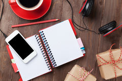 Desk with notepad, smartphone and gift boxes Stock Photos