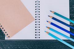 Desk with notepads and coloured pencils with empty pages and copyspace. Concept of creativity and inspiration royalty free stock photos