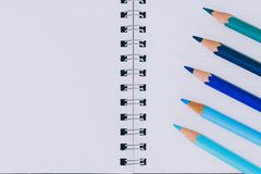 Desk with notepads and coloured pencils with empty pages and copyspace. Concept of creativity and inspiration stock photography