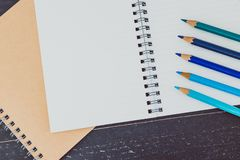 Desk with notepads and coloured pencils with empty pages and copyspace. Concept of creativity and inspiration royalty free stock photo