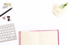 Desk in office with keyboard, pencil, colored paper clips, chrysanthemum flower and open the pink diary on a white background. Bu stock images