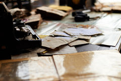 Desk in a old military office. View on a desk in a old military office. A stack of old letters tied with laces, typewriter old yellow paper, binoculars, ash tray Stock Image