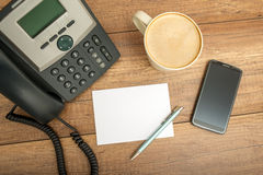 Desk phone, paper and a smart phone, on a table Royalty Free Stock Photo