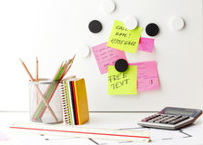 Desk with 'Post It' notes. Office work area. Desk with pink and yellow 'Post It' notes Royalty Free Stock Images