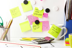 Desk with 'Post It' notes. Office work area. Desk with pink and yellow 'Post It' notes Stock Image