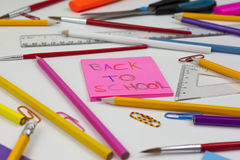 Desk scattered with pencils and a back to school note Royalty Free Stock Image