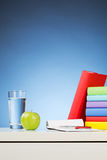 Desk with School Objects. Vertical image of a white desk with school objects on top of it - books, an apple, a glass of water and an open notepad with a pen Royalty Free Stock Photography