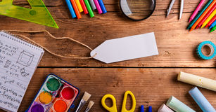 Desk, school supplies, empty tag, wooden background, copy space Royalty Free Stock Photo
