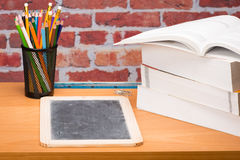 Desk with school supplies and slate Stock Images