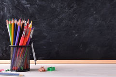 Desk with school tools and blackboard place right for title Royalty Free Stock Image