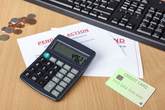 Desk showing final demands with credit card and a calculator Stock Photography