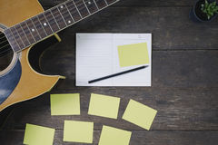 Desk of song composer for a work songwriter. Desk of song composer for a work songwriter with a guitar and notepad on wood table with vintage tone royalty free stock image