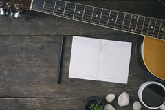 Desk of song composer for a work songwriter. Desk of song composer for a work songwriter with a guitar and notepad on wood table with vintage tone Royalty Free Stock Photography