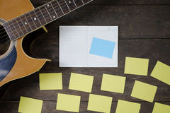 Desk of song composer for a work songwriter with a guitar. Desk of song composer for a work songwriter with a guitar and notepad on wood table with vintage tone Stock Photography