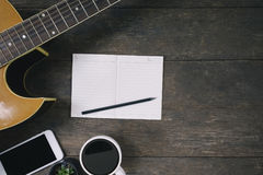 Desk of song composer for a work songwriter with a guitar. Desk of song composer for a work songwriter with a guitar and notepad on wood table with vintage tone Stock Photo