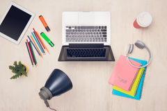 Desk with stationary and laptop on wooden background.  Stock Images