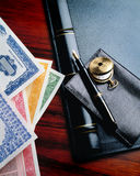 Desk with stocks. Stock certificates on desk with wallet and pen Royalty Free Stock Image