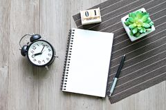 Desk table with open notebook paper, cube calendar and clock. Business, still life, working, holiday or new year planning concept : Desk table with open notebook royalty free stock photo