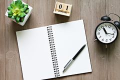 Desk table with open notebook paper, cube calendar and clock Royalty Free Stock Photography