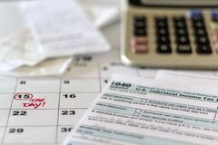Desk with tax form, receipts, calculator and calendar. Financial Accounting Taxation Concept stock photo