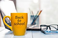Desk of teacher or student with yellow morning coffee cup with inscription - Back to school. Education concept, 1. September time stock image