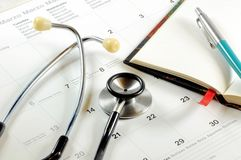 A desk top with stethoscope, notebook, pen and calendar. Stock Photos