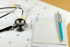 A desk top with stethoscope, notebook, pen and calendar Stock Images