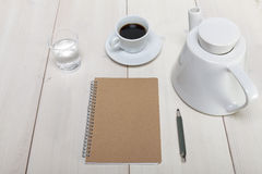 Desk top view with notebook and pencil, and coffee pot and cup a Royalty Free Stock Photos