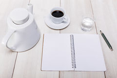 Desk top view with notebook and pencil, and fresh coffee pot and Stock Photos