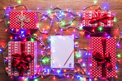 Desk view from above with empty letter to santa, presents and christmas lights, retro xmas concept Royalty Free Stock Photography