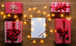 Desk view from above with letter to santa, presents and christmas lights, retro xmas concept. With copy space Stock Photo
