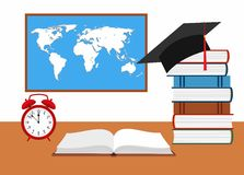 Desk with watch, hat graduate and stack of books against the background of the world map Royalty Free Stock Photo