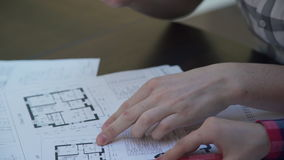 At a desk a woman and a man with a pizza look floor plan on paper. stock video footage