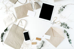 Desk workspace with tablet, phone, craft envelopes and eucalyptus branches Royalty Free Stock Image