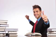 At desk writing & thumb up Stock Photo