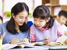 Deskmates asiatiques d'école primaire ayant une discussion Images libres de droits