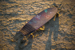 Deskorolka lub longboard wtykaliśmy w piasku w pustyni przy zmierzchem Fotografia Stock