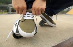 Deskorolkarz wiąże shoelace przy skatepark rampą Fotografia Royalty Free