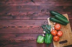 deskowi świeże warzywa rozbioru pomidor, ogórek, dzwonkowy pieprz, czosnek Fotografia Royalty Free