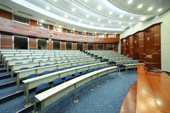 Desks and blue seats in empty university auditorium Stock Images