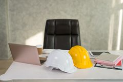 Desks of engineers with laptops,safety helmet, digital tablet. In the office royalty free stock image