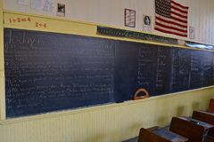 Desks of a one room schoolhouse. Old wood school desks, lessons on blackboards, chalk, and rulers in a one room rural schoolhouse stock image