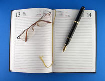 Desktop. Pen, eyeglasses, scheduler Stock Photos