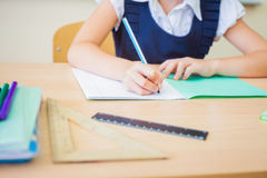 Desktop background of student sitting at desk for classwork. Desktop background of student sitting at a desk, holding a pen and ready to writing in a notebook stock photography