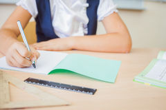 Desktop background of student sitting at desk for classwork. Desktop background of student sitting at a desk, holding a pen and ready to writing in a notebook royalty free stock photography