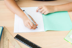 Desktop background of student sitting at desk for classwork. Desktop background of student sitting at a desk, holding a pen and ready to writing in a notebook stock image