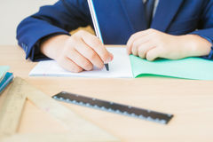 Desktop background of student sitting at desk for classwork. Desktop background of student sitting at desk, holding pen and ready to writing in a notebook for royalty free stock photography