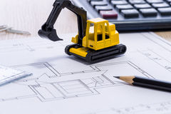 Desktop with blueprint yellow mini excavator, ruler and pencil Stock Images