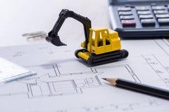 Desktop with blueprint yellow mini excavator, ruler and pencil Stock Photo