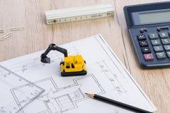 Desktop with blueprint yellow mini excavator, ruler and pencil Stock Image